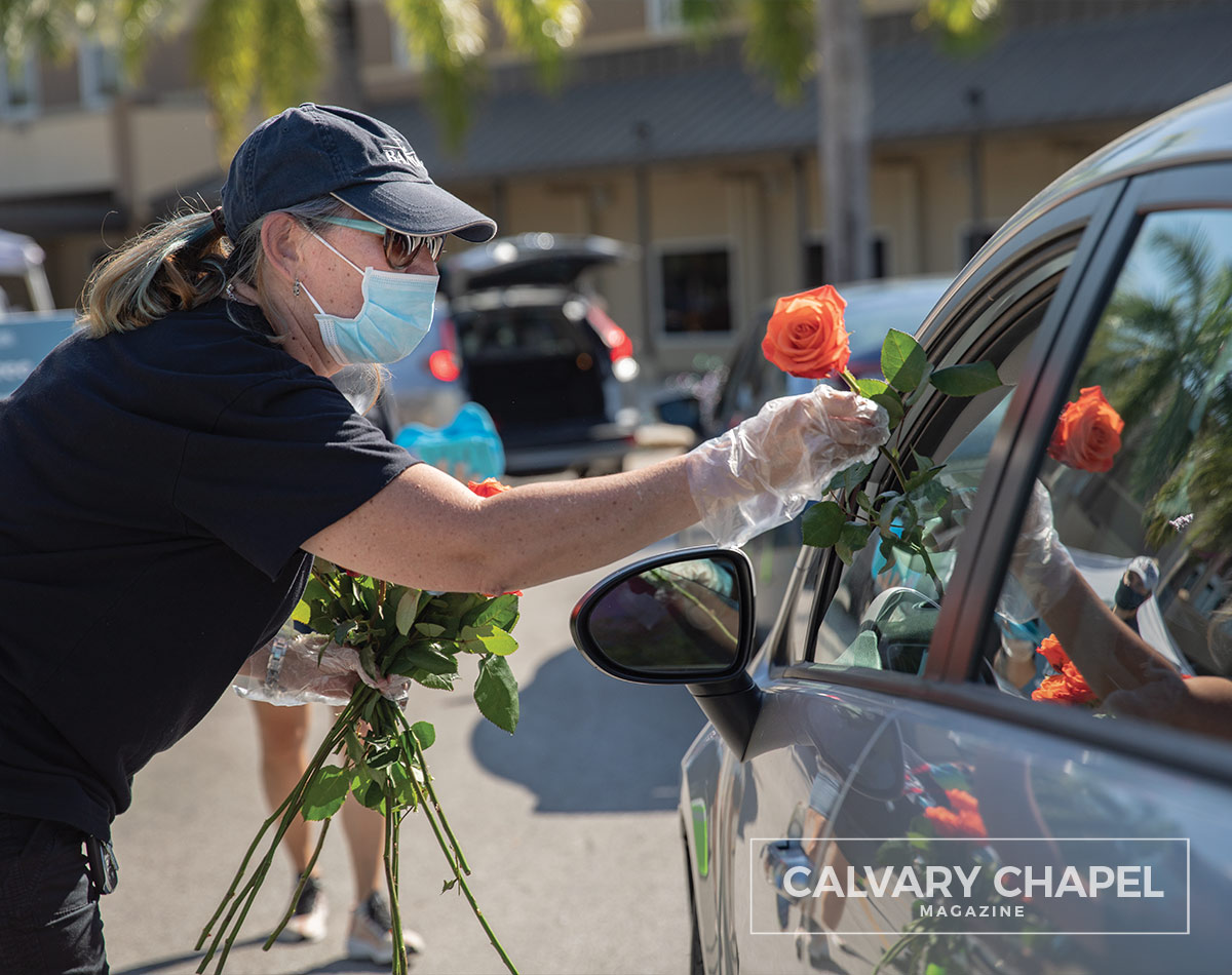handing a rose to a lady in car