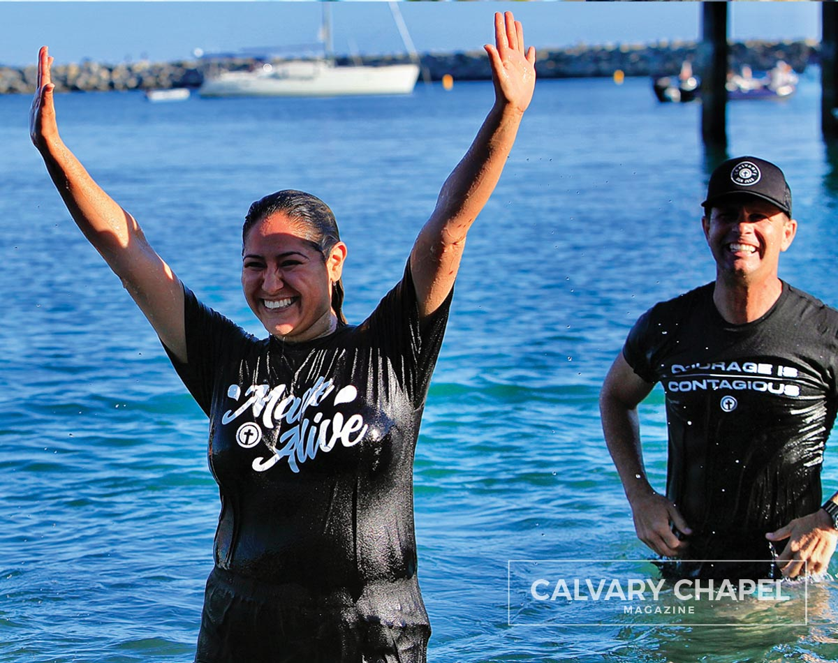 Lady holding up arms in victory after baptism