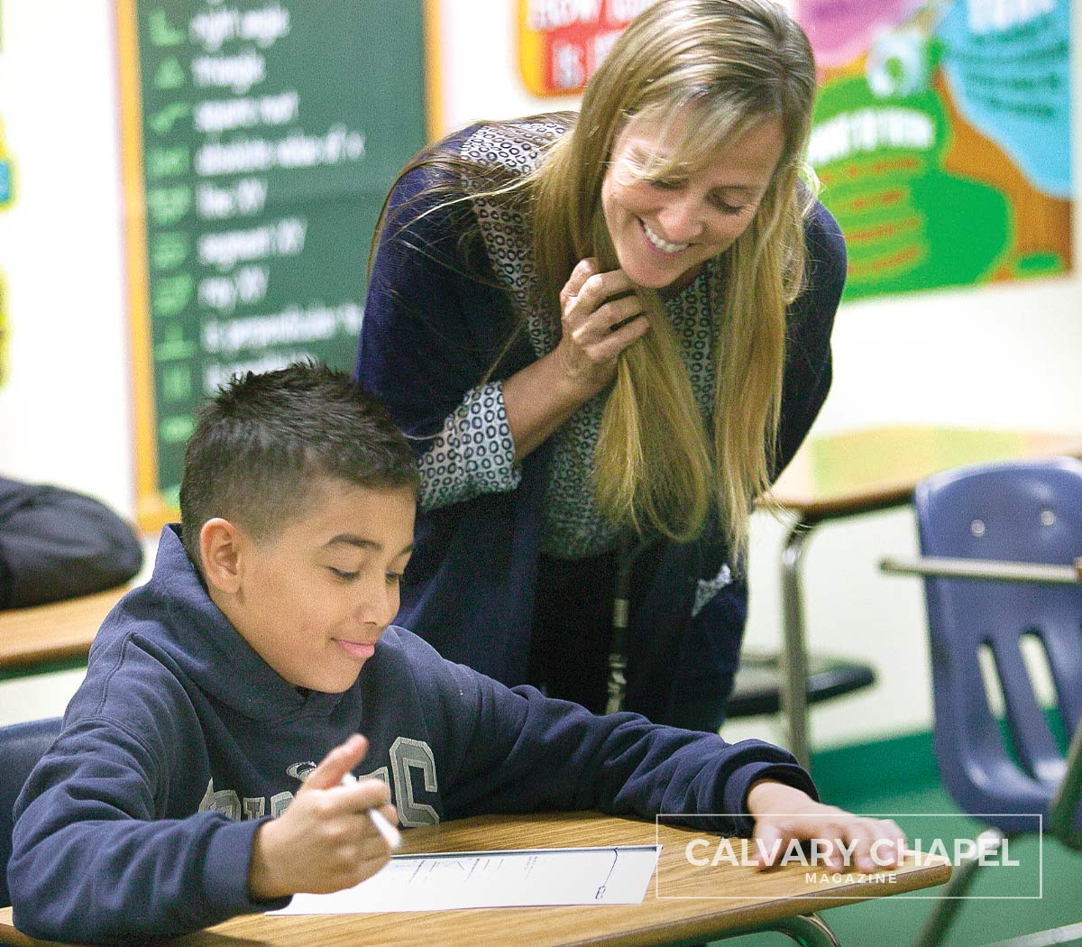 Woman helping boy with classwork