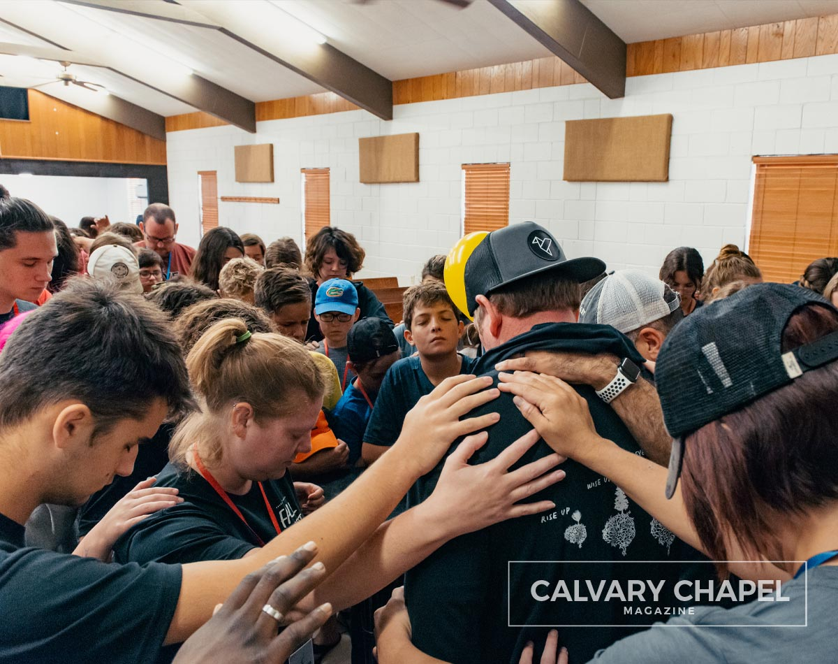 Youth praying for pastor