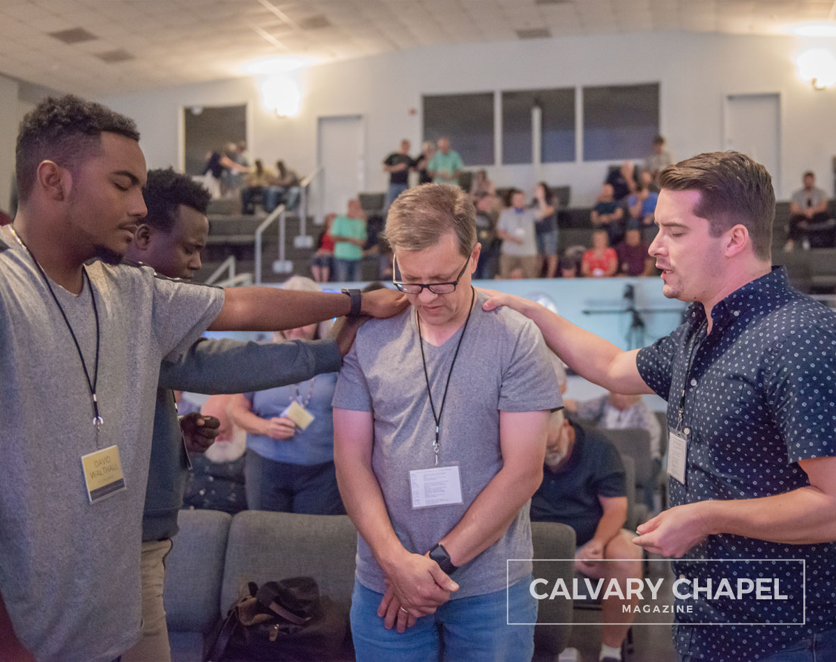 Young men praying for older pastor