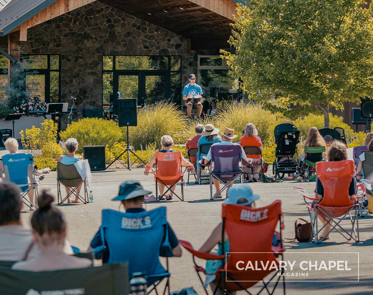 Pastor preaching believers sitting in lawn chairs