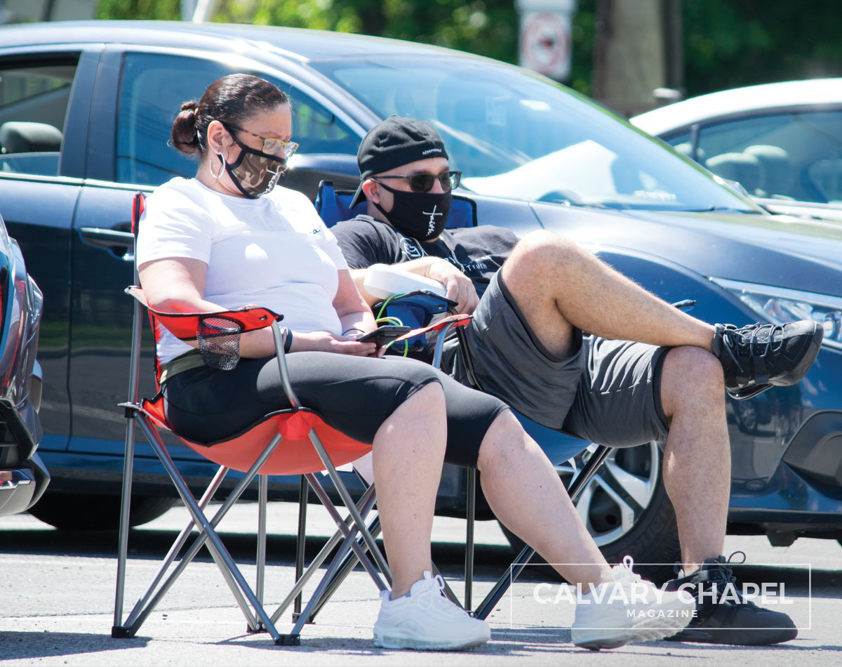 couple wearing masks on lawnchairs in parking lot