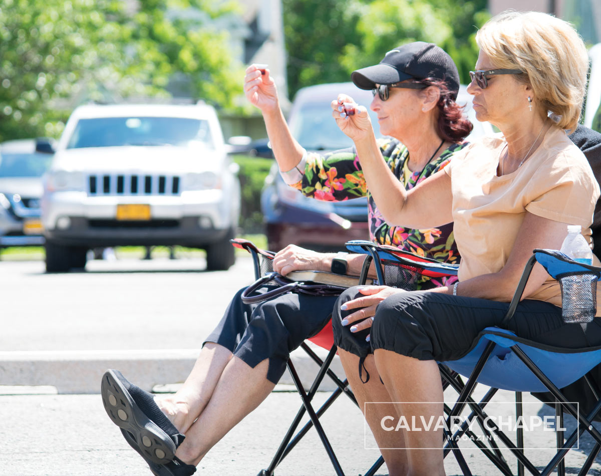 ladies in lawn chairs take communion in parking lot
