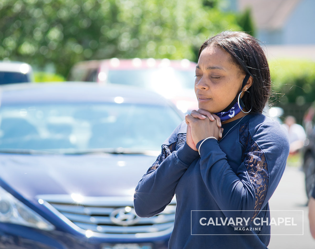 lady clasps hands in prayer in parking lot