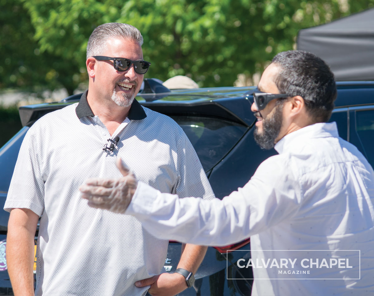 Pastor Johny fellowships with man in parking lot