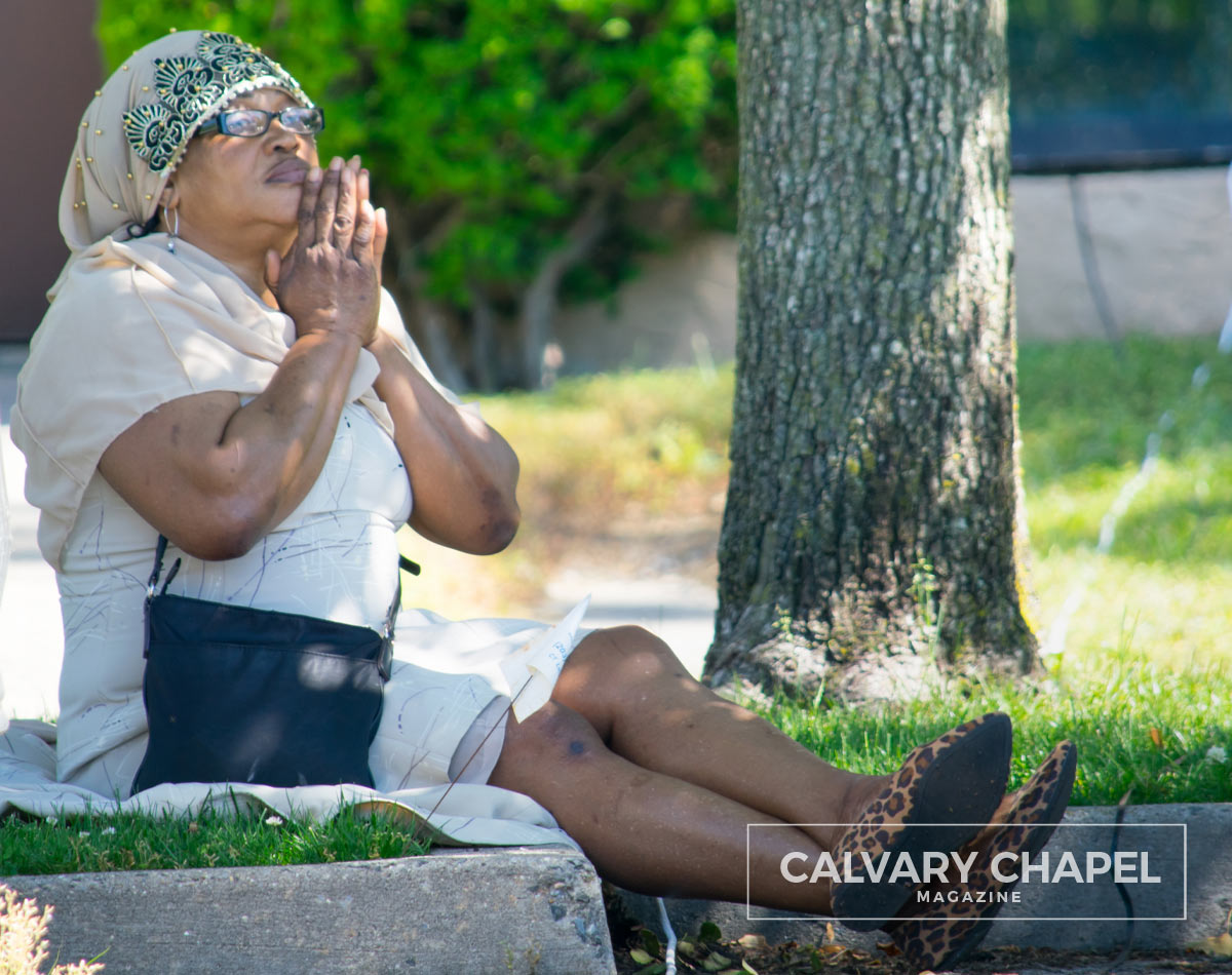 lady sits on curb in parking lot praying