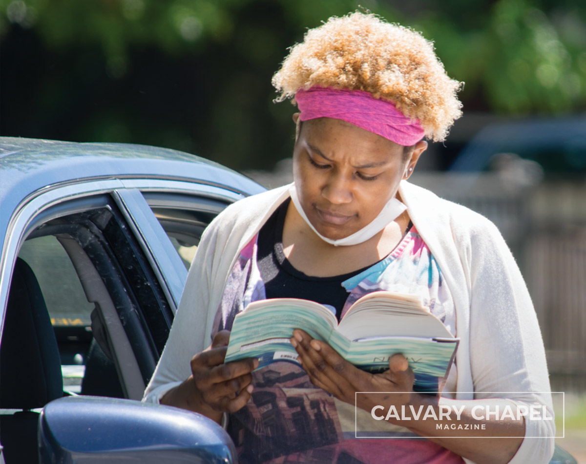 A woman reads the Bible standing near a car in a parking lot