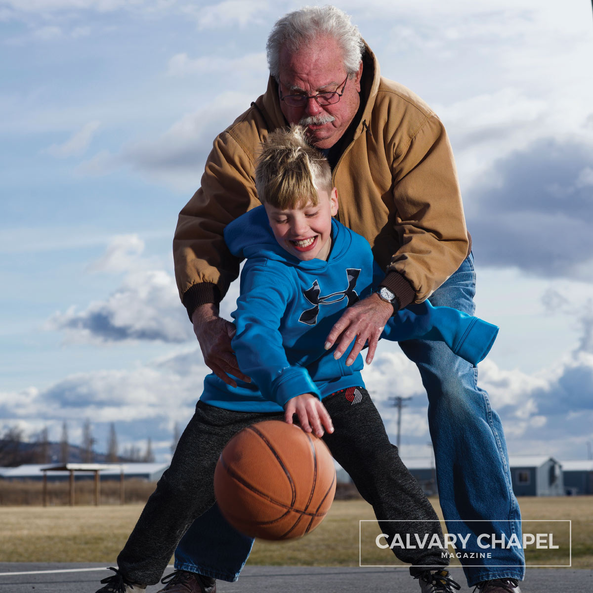 Man and his grandson play with a basketball