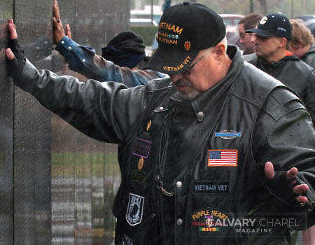At the wall, Veteran Ernie Salas prays for the families of service people who gave their lives in Vietnam.
