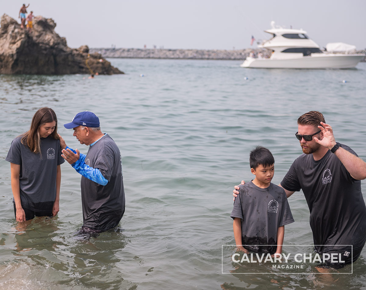 Men baptize kids with boat in background and kids jumping off rocks
