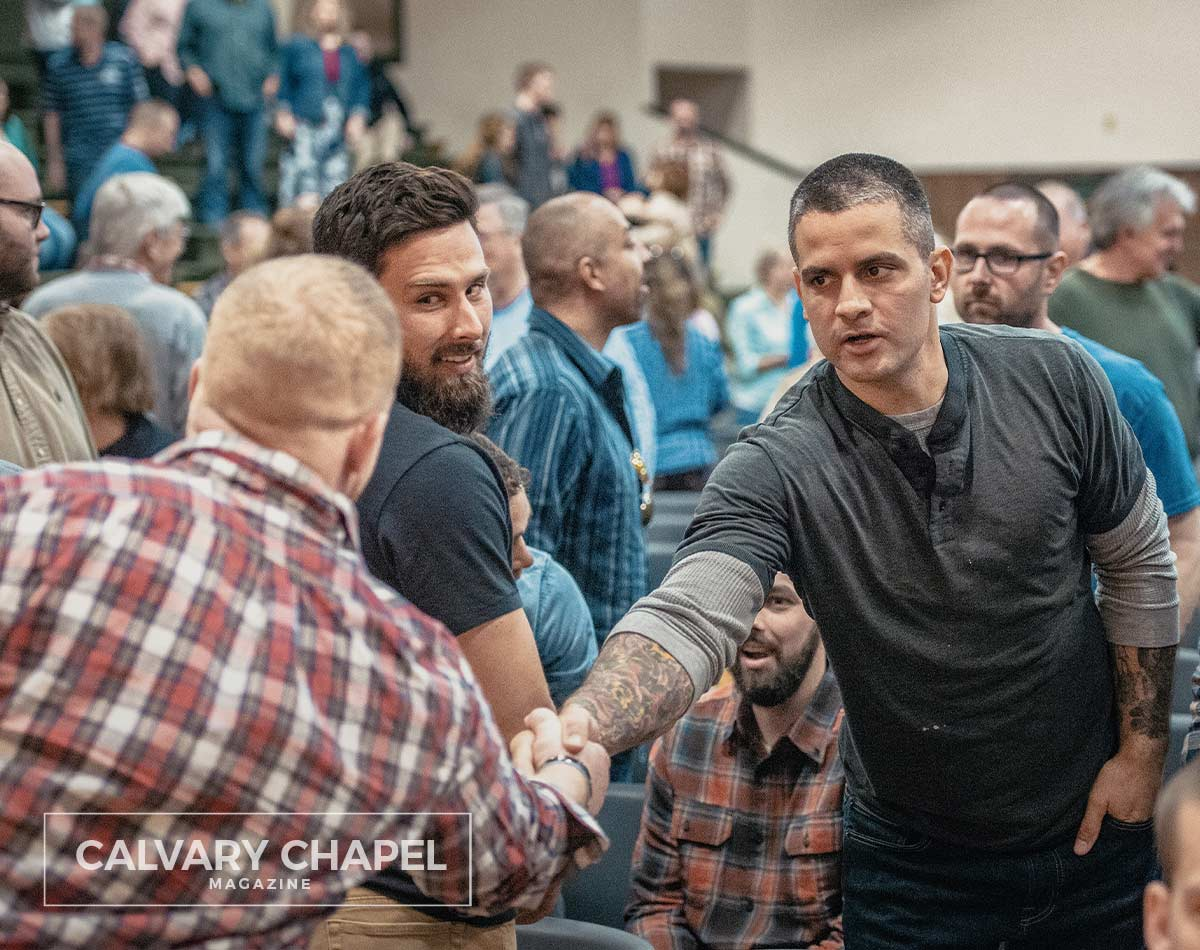 men greet each other at church