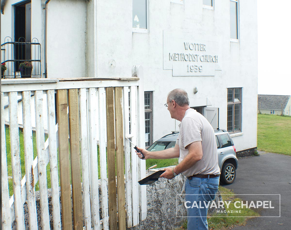 Man painting fence by church