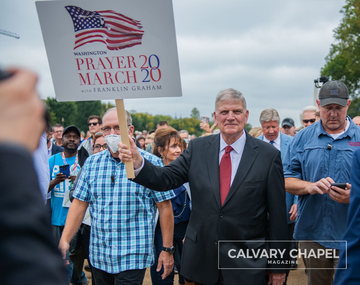 Franklin Graham marches and holds sign