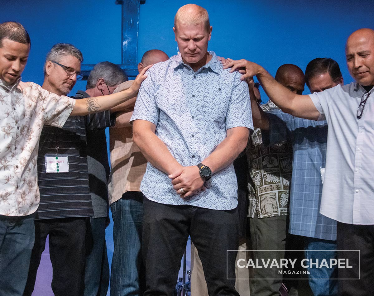 Pastors and elders laying hands on Pastor Phil