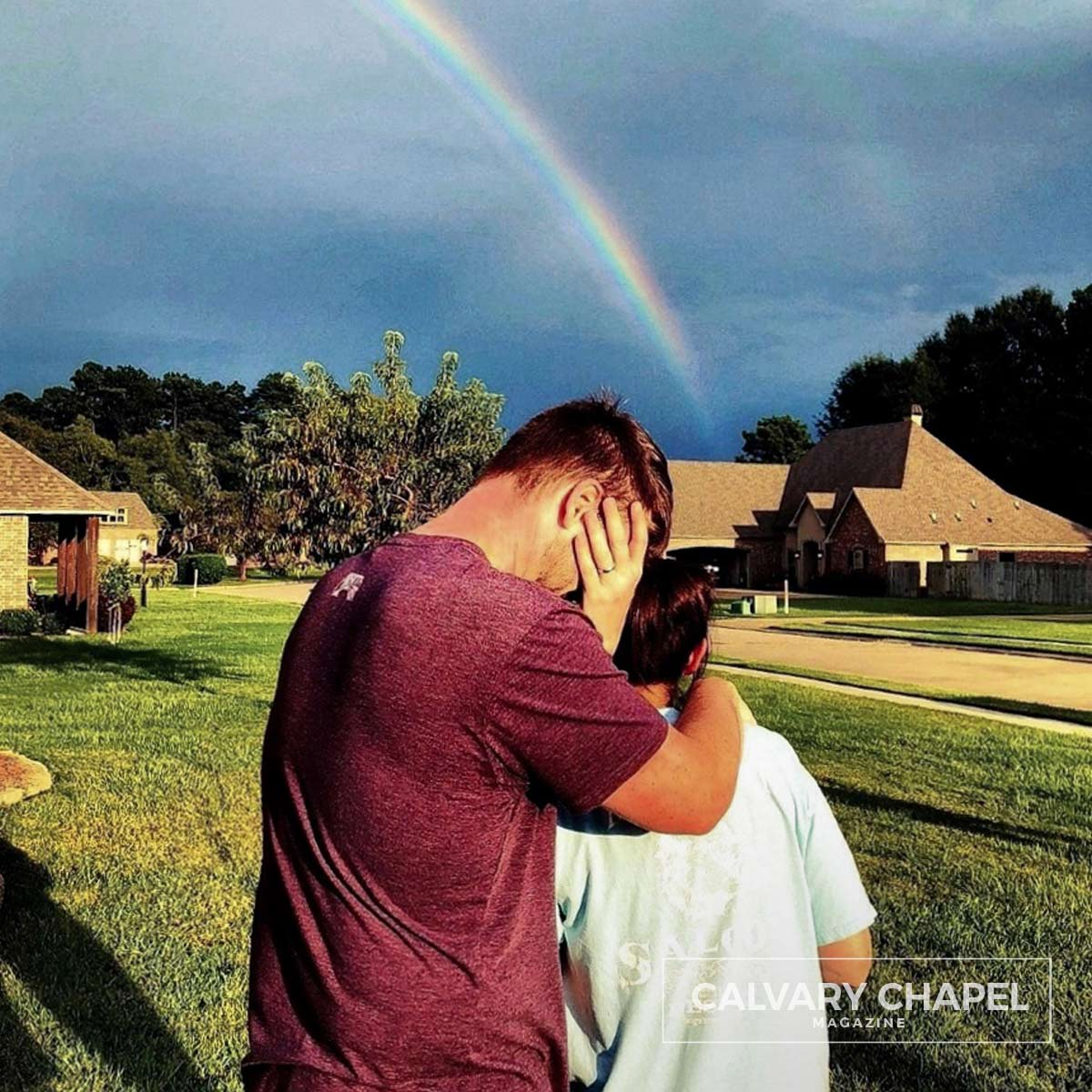 Man and woman hug under a rainbow