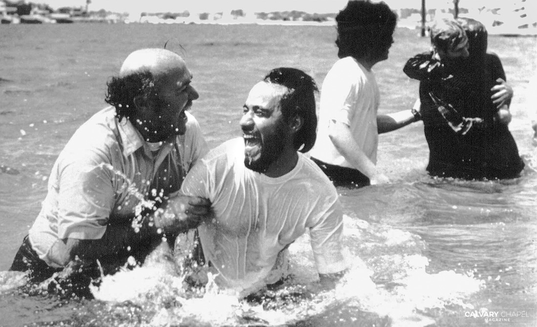 Pastor Chuck baptizing new believers with a joyful heart