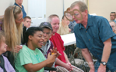 "During a teaching game, Chris interacts with Shatoya Brown while wearing ""grace-colored glasses."" The attendees eagerly anticipate the Bible lessons, and they love to participate in the games and activities that illustrate the truths they are learning."