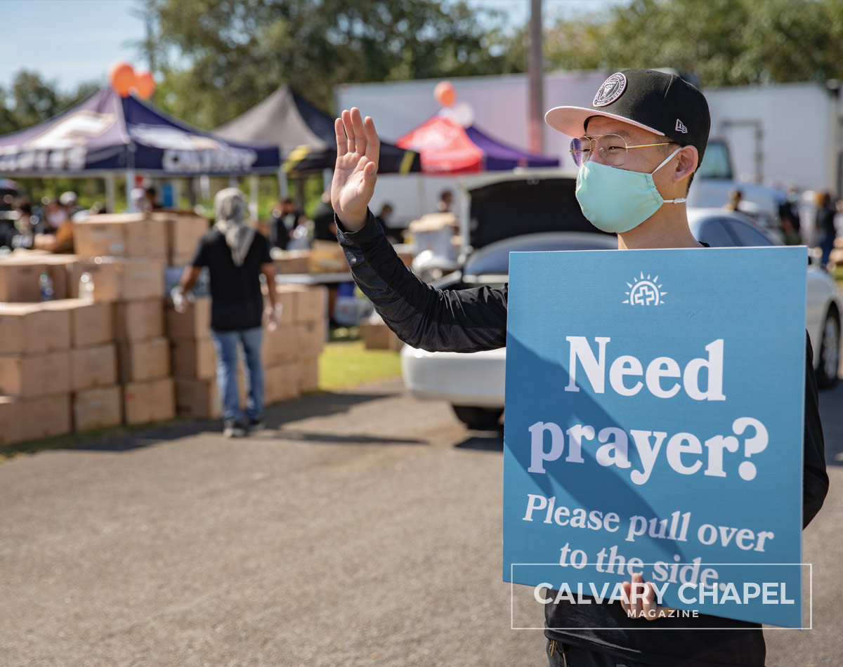 "Waving with sign that says ""Need prayer?"""