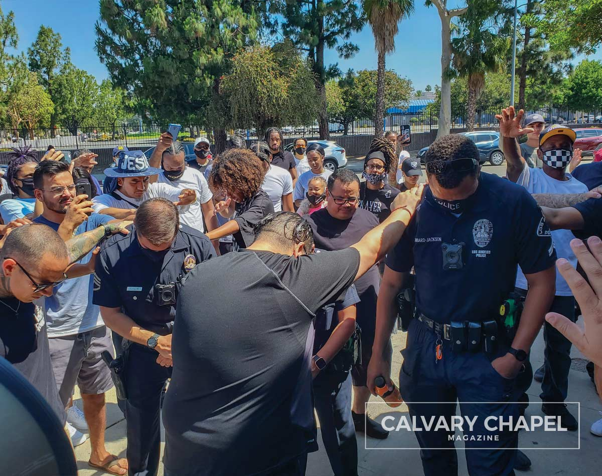 People laying hands and praying for police