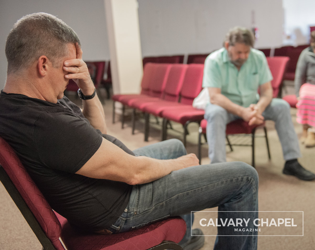 Pastor Mike praying with others