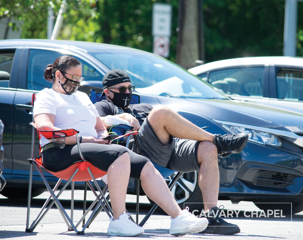 Couple with masks sitting in lawn chairs